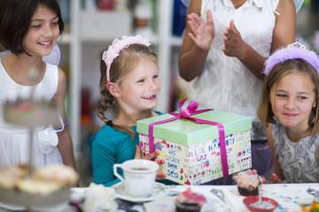 Mädchen erhält Geschenk auf einer Geburtstagsparty