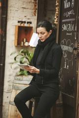 Spanien, Katalonien, Barcelona, __junge schwarze gekleidete Geschäftsfrau guckt auf ihr Smartphone vor einer Weinstube