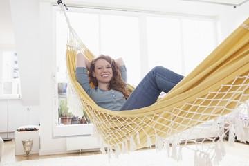 Lächelnde Frau entspannt in einer Hängematte in ihrer Wohnung