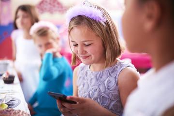 Mädchen mit Handy auf einer Geburtstagsparty