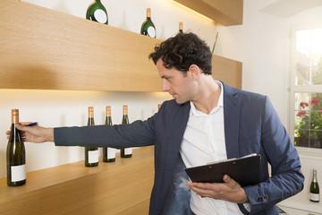 Mann überprüft Flasche Wein