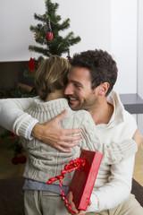 Vater gibt seinem Sohn Weihnachtsgeschenk