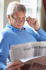 Mann liest Zeitung, zu Hause