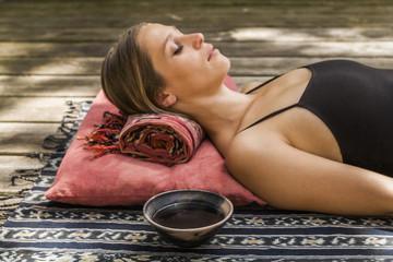 Frau auf Holzterrasse beim meditieren