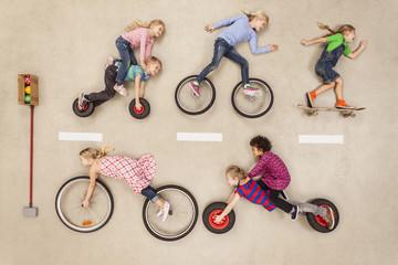 Kinder <fahren Fahrrad und Skaten auf der Straße