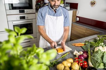 Österreich, Mann in der Küche hackt Karotten