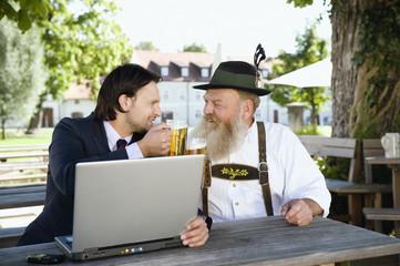 Deutschland, Bayern, Oberbayern, Bayer und junger Geschäftsmann mit Laptop im Biergarten