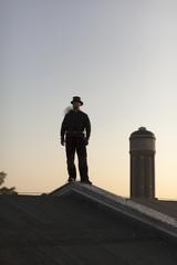 Deutschland, Schornsteinfeger auf dem Dach in der Dämmerung