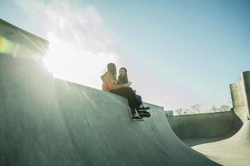 Zwei Jugendlichen im Skatepark mit Handy