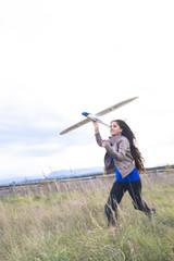 Junge Frau auf einer Wiese mit Modellflugzeug