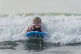Junge mit Surfbrett zeigt Victory-Zeichen