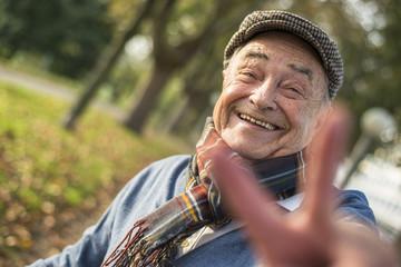 Portrait eines glücklichen Senioren, Victory-Zeichen