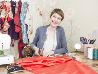 Porträt der lächelnden Modedesignerin an ihrem Schreibtisch