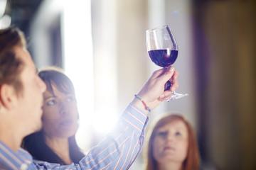 Mann und zwei Frauen begutachten Rotwein