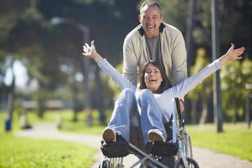 Mann schiebt begeistert Frau im Rollstuhl