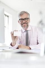Portrait der lächelnde Mann am Schreibtisch zeigt seine Visitenkarte