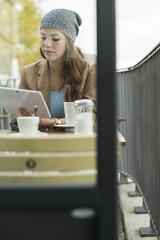 Junge Frau sitzt im Café mit Tablet - PC