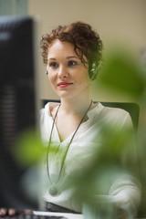 Junge Frau im Büro trägt Headset