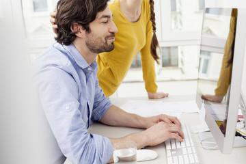 Paar im Arbeitszimmer mit Mann am Computer
