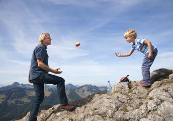 Deutschland, Bayern, Vater und Sohn (4-5 Jahre) spielen auf Berggipfel