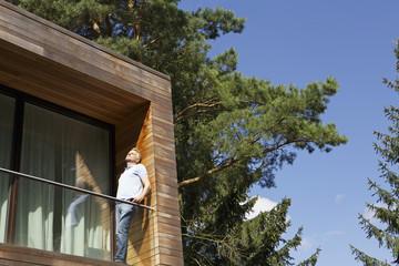 Deutschland, Berlin, Älterer Mann stehen auf dem Balkon und entspannt