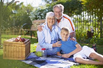 Großeltern mit Enkel bei einem Picknick im Park
