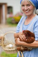 Deutschland, Bayern, Ältere Frau mit Korb mit frischen Eiern und Hühnerfleisch