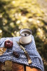 Kaffee, Äpfel, Trauben und Blätter auf hölzerner Bank