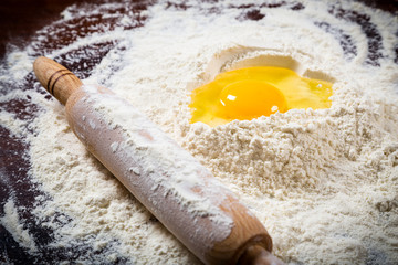 Flour, egg and rolling pin on table