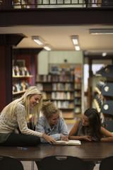 Drei weibliche Studenten in einer Bibliothek