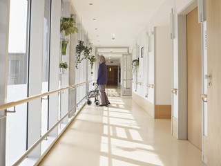 Deutschland, Köln, Seniorin mit Gehhilfe auf Gang in Pflegeheim