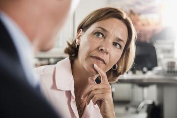 Ernste Frau blickt auf Geschäftsmann