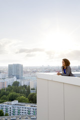 Deutschland, Berlin, junge Frau auf der Dachterrasse, geniesst die Aussicht