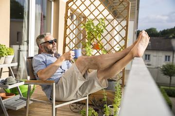 Mann mit Sonnenbrille entspannt auf seinem Balkon mit einer Tasse Kaffee