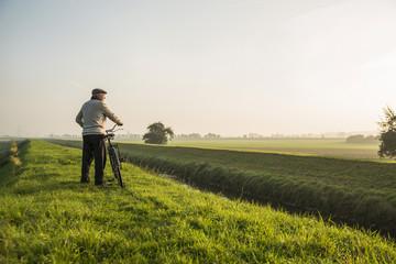 Älterer Mann in ländlicher Gegend schiebt Fahrrad