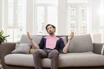 Enttäuschter Mann mit rosa Babyhemd auf der Couch