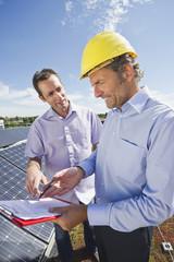 Deutschland, München, Mann im Gespräch mit Ingenieur in Solaranlage