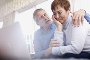 Älterer Mann, der die Frau tröstet, am Laptop