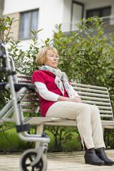 Ältere Frau mit Rollator sitzt auf einer Bank