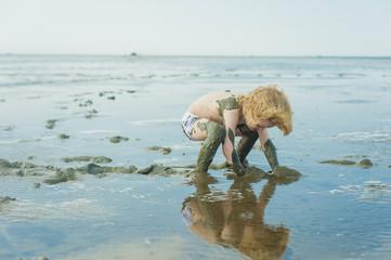 Deutschland, Schleswig Holstein, Junge spielt im Schlamm am Strand