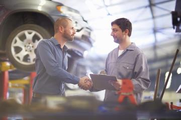 Automechaniker und Kunde, Händeschütteln in Reparaturwerkstatt