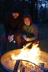 Vater und Sohn rösten Marshmallows am Lagerfeuer