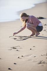 Junge Frau, Zeichnung von Herzen inden  Sand am Strand