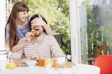Frau füttert Mann am Frühstückstisch