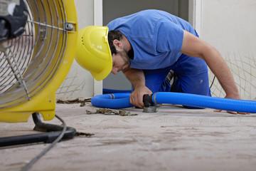 Arbeiter mit Luftentfeuchter in einer Wohnung, die durch Hochwasser beschädigt wurde