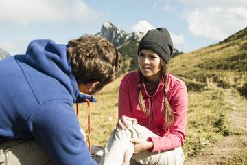 Österreich, Tirol, Tannheimer Tal, junger Mann kümmert sich um verletzte Frau auf Wanderung