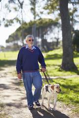 Sehbehinderter Mensch zu Fuß mit seinem Blindenhund in einem Park