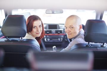 Lächelndes Paar beim Autohändler, im Auto