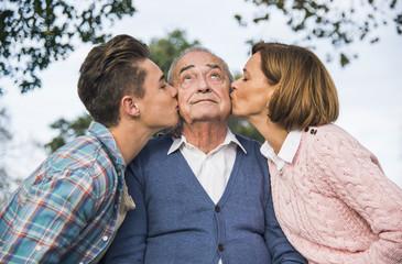 Enkel und Tochter küssen älterem Mann auf die Wange