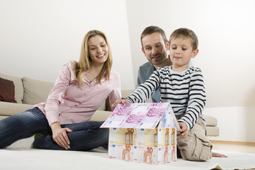Eltern und Sohn (4-5), bauen Haus aus Euro-Banknoten